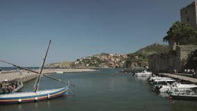 Collioure, Γαλλία Βάρκες που δένονται στο αγκυροβόλιο κοντά στην εκκλησία της κυρίας μας των αγγέλων πέρα από τον κόλπο στην ηλιό απόθεμα βίντεο