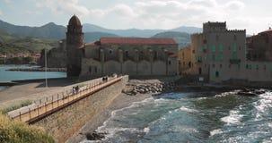 Collioure, Γαλλία Τουρίστες ανθρώπων που περπατούν στην ακτή κοντά στην εκκλησία της κυρίας μας των αγγέλων πέρα από τον κόλπο τη φιλμ μικρού μήκους