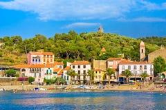 COLLIOURE, FRANÇA - 5 DE JULHO DE 2016: Encalhe hotéis na vila de Collioure com um moinho de vento na parte superior do monte, Ro imagens de stock royalty free