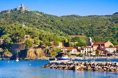 COLLIOURE, FRANCE - JULY 5, 2016: Beach hotels in Collioure village with a windmill at the top of the hill, Roussillon, Vermilion Royalty Free Stock Images