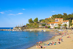 COLLIOURE, FRANCE - JULY 5, 2016: Beach hotels in Collioure village with a windmill at the top of the hill, Roussillon, Vermilion Stock Images