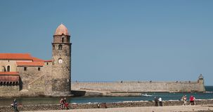 Collioure, France - May 16, 2018: People Tourists Resting And Walking In Coast Near Church Of Our Lady Of The Angels. Across The Bay In Sunny Spring Day stock video