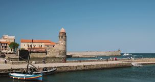 Collioure, France. People Tourists Resting And Walking In Coast Near Church Of Our Lady Of The Angels Across The Bay In. Sunny Spring Day stock video footage