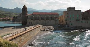 Collioure, France. People Tourists Walking In Coast Near Church Of Our Lady Of The Angels Across The Bay In Sunny Spring. Day stock footage