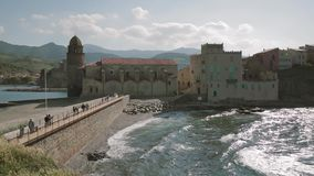 Collioure, France. People Tourists Walking In Coast Near Church Of Our Lady Of The Angels Across The Bay In Sunny Spring. Day stock video