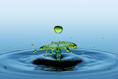 Collision effect of two green falling water drops - splatter. Water splatter and splash. Collision effect of two green falling rain drops royalty free stock images