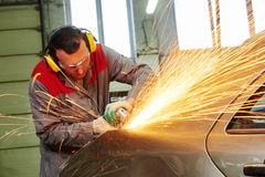 Collision repairs service. mechanic grinding car body by grinder Stock Image