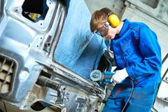 Collision repairs service. mechanic grinding car body by grinder Royalty Free Stock Images