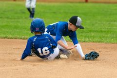 Collision at second base. Youth baseball player in blue uniform playing short stop withstanding base runner sliding into the base in a cloud of dust stock photo
