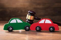 Collision Of Wooden Two Toy Cars In Front Of Gavel. On The Wooden Table royalty free stock photos