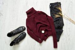 Collo alto del Bordeaux, stivali neri, orologi e jeans strappati Spik Fotografia Stock Libera da Diritti