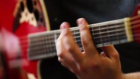 Collo della chitarra del primo piano e mano del chitarrista video d archivio