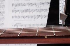 Collo, note e metronomo della chitarra del primo piano Fotografie Stock Libere da Diritti