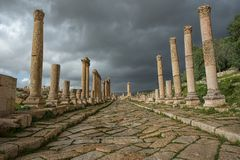 A  collonade street in the ancient city of Gerasa after a storm. With dark grey clouds Royalty Free Stock Image