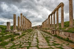 A  collonade street in the ancient city of Gerasa after a storm. With dark grey clouds Stock Images