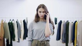 Colloqui allegri della giovane donna sullo smartphone in una stanza dell'abbigliamento stock footage