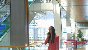 Colloqui allegri di una donna di affari dopo la compera in un centro commerciale sullo smartphone e sulle risate stock footage