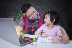 Colloqui dell'insegnante con il suo studente nella classe Immagini Stock