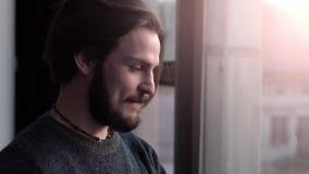 Colloqui dell'uomo sul telefono vicino alla finestra video d archivio