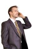Colloqui sorridenti dell'uomo d'affari sul telefono Fotografia Stock