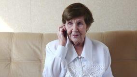 Colloqui sorridenti della donna anziana sul telefono cellulare Fine in su archivi video