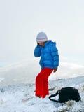 Colloquio della ragazza dal cellulare sul plateau di inverno della montagna fotografie stock