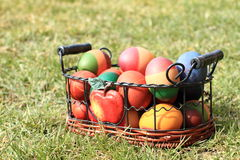 Eggs in a basket. Collored easter eggs in a wicker-work - metal basket lying on the green grass Stock Photo
