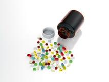 Collorful preventivpillerar som spills från flaskan Arkivbild