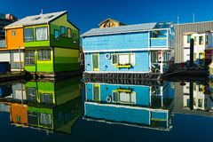 Colorful village of float homes on bright sunny day, blue sky. stock photos