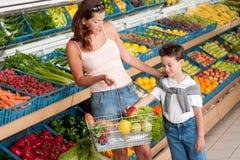 Colmado - madre con la fruta de compra del niño Foto de archivo