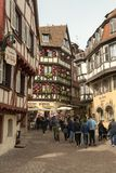 Tourists walking through streets in old mediaval city of Colmar. COLMAR, FRANCE - APRIL 2, 2018: Tourists walking through streets in old mediaval city of Colmar stock photo
