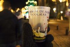 COLMAR, FRANCE - 29 DÉCEMBRE 2017 : Verres de Noël pour le vin chaud chaud dans les mains d'un touriste dans la perspective de images libres de droits
