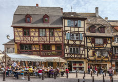 Colmar Lifestyle. Colmar,France- April 23rd, 2011: People relaxing on street terraces in a town square near traditional half-timbered houses in Colmar, Alsace Stock Photography