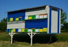 Colmenas coloridas de la abeja con el cielo azul Imagenes de archivo