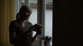 Coloc?ndose en la ventana, una mujer que lleva a cabo una imagen en un marco, mir?ndola y frotando ligeramente su mano metrajes