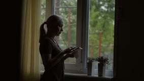 Coloc?ndose en la ventana, una mujer que lleva a cabo una imagen en un marco, mir?ndola y frotando ligeramente su mano almacen de metraje de vídeo