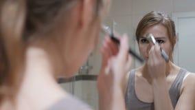 A colocação da jovem mulher compõe na cara no espelho filme