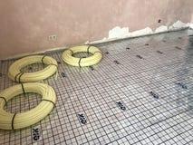 Colocação de assoalhos mornos em uma casa privada A tubulação de aquecimento é colocada no assoalho e fixada Imagens de Stock Royalty Free