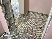 Colocação de assoalhos mornos em uma casa privada A tubulação de aquecimento é colocada no assoalho e fixada Foto de Stock