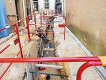 A colocação de cabos subterrâneos das comunicações em uma rua estreita de uma cidade medieval europeia fotografia de stock royalty free