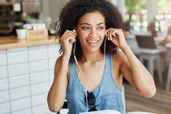 Colocação de sorriso da menina africana bonita feliz sobre os fones de ouvido que sentam o descanso no café Fotos de Stock Royalty Free
