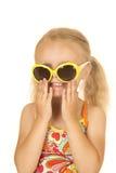 Colocação de sorriso da menina loura parva sobre seus óculos de sol Fotografia de Stock