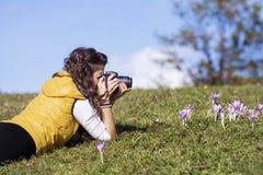 Colocação do fotógrafo da jovem mulher exterior Fotos de Stock