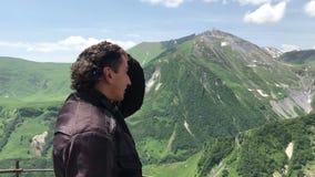 A colocação do turista do homem do capacete da motocicleta e olhar ao redor na opinião do ponto em montanhas caucasianos verdes v vídeos de arquivo