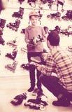 A colocação masculina do vendedor patina no cliente do menino no stor dos esportes imagem de stock royalty free