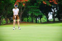 Colocação verde do jogador do jogador de golfe Imagens de Stock Royalty Free