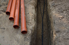Colocación de cables y de tubos en el foso Fotografía de archivo