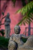 Colocación de la estatua de piedra de Buda en jardín Imagen de archivo libre de regalías
