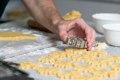 Colocación de las galletas después de cortar en el papel del forro Imagenes de archivo