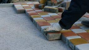 Colocación de las losas por el primer del mosaico Camino que pavimenta, construcción almacen de metraje de vídeo